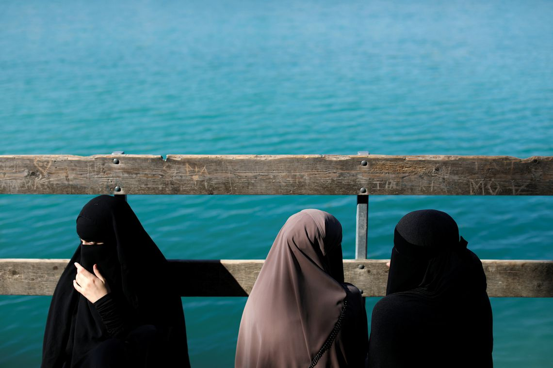 """Alaa (L), 21, Amina (C), 24, and Nayab, 18, sit on a dock during a visit to Karlstrup Kalkgrav, a lake near Karlstrup located outside Copenhagen, Denmark, July 19, 2018.  REUTERS/Andrew Kelly    SEARCH """"DENMARK VEIL"""" FOR THIS STORY. SEARCH """"WIDER IMAGE"""" FOR ALL STORIES. TPX IMAGES OF THE DAY. THE IMAGES SHOULD ONLY BE USED TOGETHER WITH THE STORY - NO STAND-ALONE USES"""