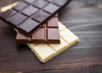 Delicious and sweet chocolate bars on wooden background