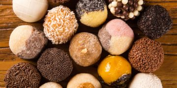 Traditional brazilian sweets - brigadeiros - over wood background.